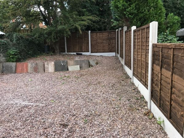 A wooden fence with z type timber panels, double framed, horizontally overlapped with bevelled capping.