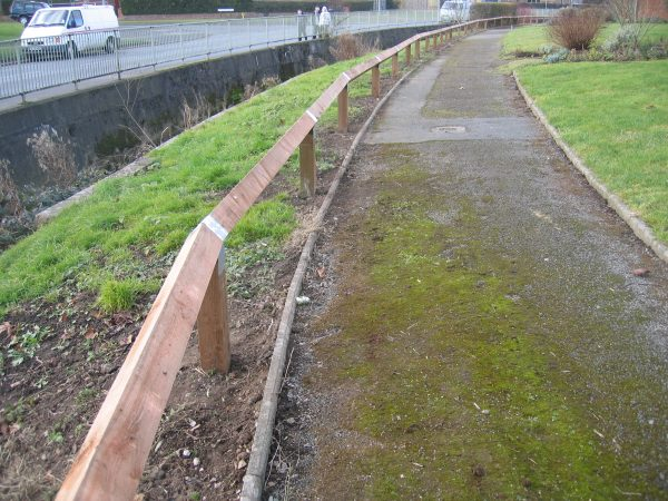 Bird mouth posts alongside a public walkway. The posts are pressure treated with a galvanised strap on each post.