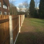 A wooden fence with concrete fence posts on display in a fencing suppliers in Birmingham.