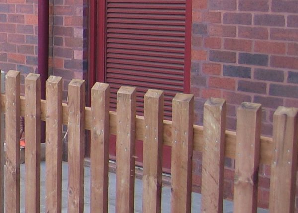 A wooden fence standing in front of a commercial building. The fence is constructed using timber pales.