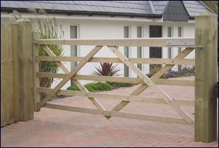 A house with a field gate securing the property. The timber field gate supported by timber gate posts.
