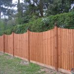 A wooden fence runs along the perimeter of a building. It is a warm wood and stands horizontally by two trees.