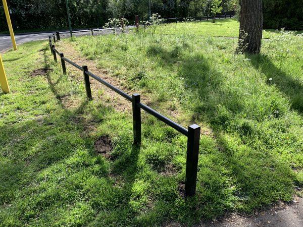 Steel trip rail along the perimeter of a open grassy area.