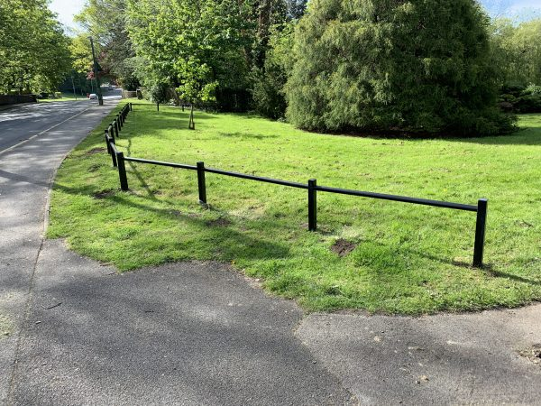 A open space with a steel trip rail separating a grass space from a public path.