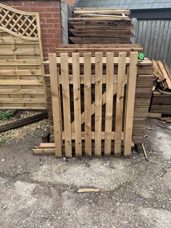 A wooden paling gate is stood horizontally against wooden posts in a stocked supply yard.
